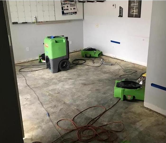 Two air movers and a humidifier drying up an office after a severe storm damage